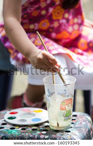 Little girl mixing color to paint on easel - stock photo