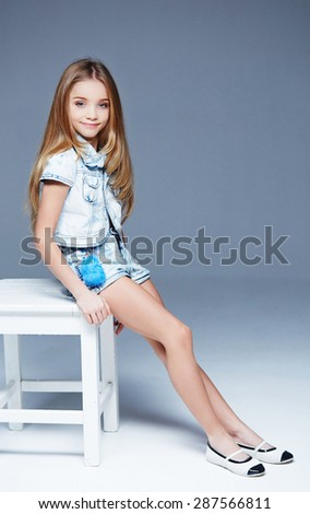 Little girl model with long hair and blue eyes posing on light grey background. - stock photo
