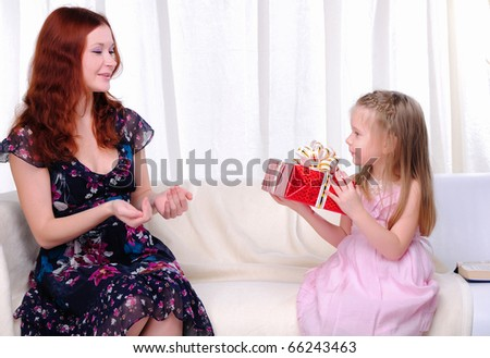 Little girl mom gives a holiday gift in red box with white ribbon.