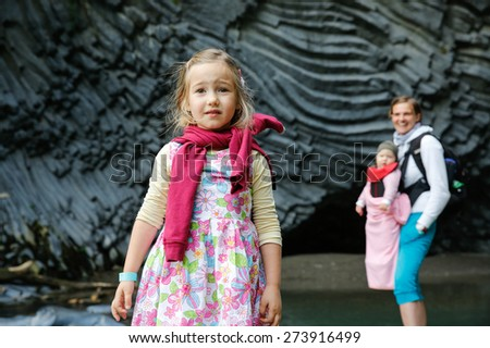 Little girl, mother and baby in kangaroo carrier enjoying the sights of Golle del Alcantara gorge with hexagonal volcanic rock columns, foothill of Mt. Etna, Sicily, Italy. Family travel concept. - stock photo