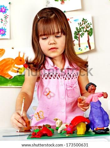 Little girl  moulding of plasticine . - stock photo
