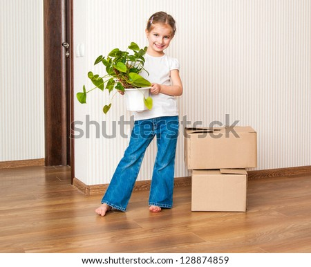 Little girl moving into new house, carrying cardboard box and green plant - stock photo