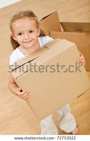 Little girl moving into new house, carrying cardboard box - top view - stock photo