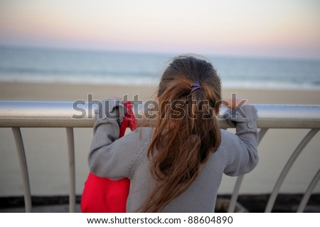 Little girl musing upon a distant scene on ocean shore - stock photo