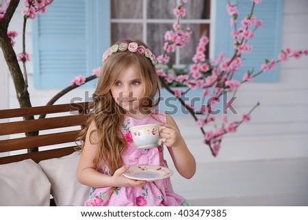 Little girl near a house and sakura drinking tea - stock photo