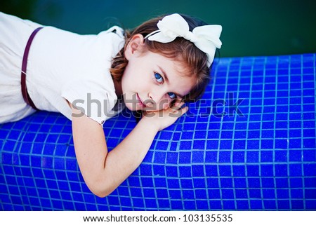 Little girl near swimming pool - stock photo