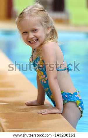 little girl  near the open-air swimming pool