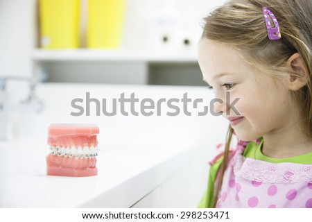 Little girl observing artificial model of human jaw with dental braces in dentists office, smiling. Paediatric dentistry, aesthetic dentistry, early education and prevention concept.   - stock photo