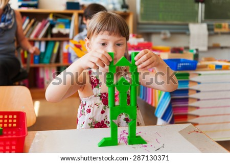 Little girl of 5 years old building a structure in a classroom - stock photo