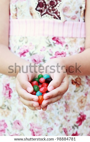Little girl offering a handful of jellybeans. Extreme shallow depth of field with selective focus on little girls fingers and jellybeans in foreground. - stock photo