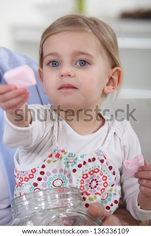 Little girl offering marshmallows - stock photo