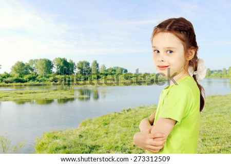 Little girl on a bank of the river in summer - stock photo