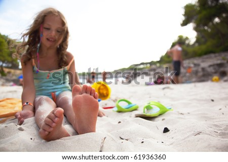 little girl on a beach. focus on foots - stock photo