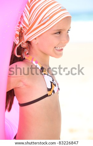Little girl on a beach with a rubber ring - stock photo
