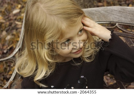 Little girl on a bench - stock photo