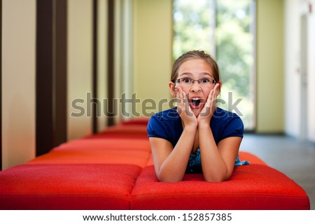 Little girl on a bench in a sunny room gesturing with room for copy - stock photo