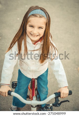 Little girl on a bicycle in summer park - stock photo
