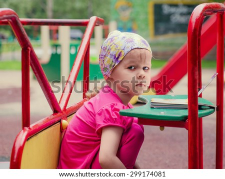 Little girl on a Carnival Carousel at an amusement park or theme park. Warm afternoon sun in the background - stock photo