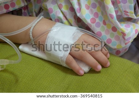 little girl on a drip receiving a saline solution in hospital - stock photo