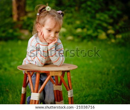 Little girl on a green lawn leans against chair and thinks of mother. - stock photo