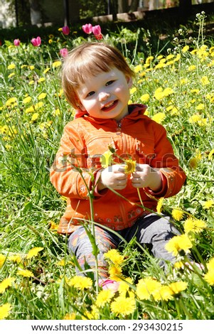 little girl on a green meadow with dandelions in spring