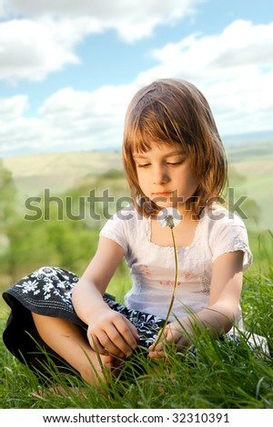 Little girl on a meadow with dandelion. - stock photo