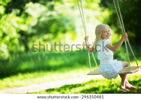 Little girl on a swing - stock photo