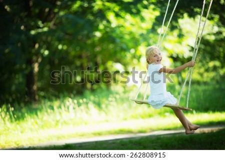 Little girl on a swing in the park - stock photo