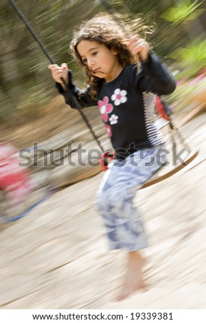 little girl on a swing with motion blure