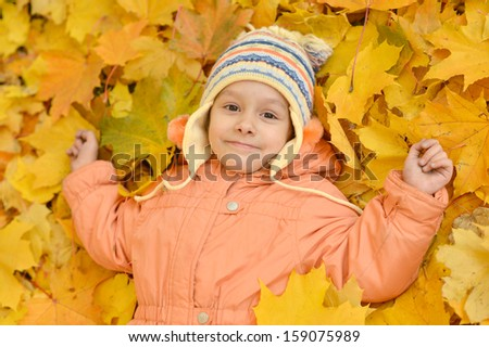 little girl on a walk during the fall of the leaves in the park
