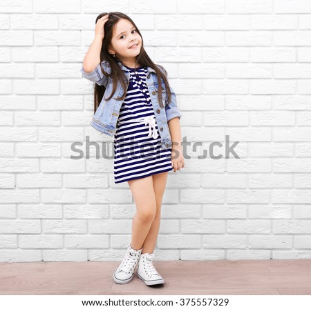 Little girl on a white brick wall background - stock photo