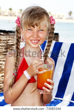 Little girl on beach drinking cocktail. - stock photo
