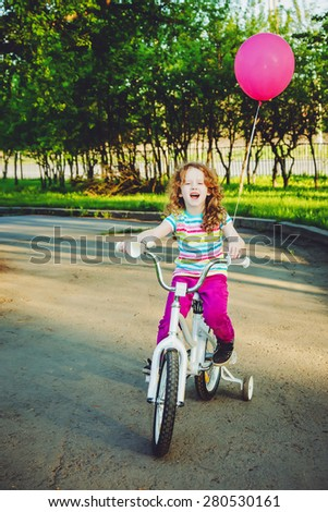 Little girl on bicycle in the park,  background toning for instagram filter. - stock photo