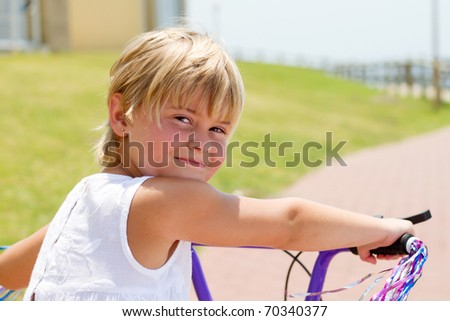 little girl on bicycle outdoors - stock photo