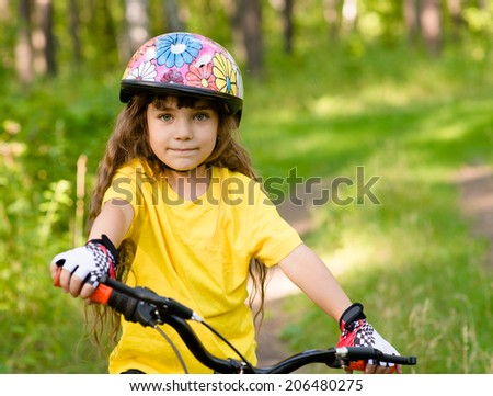 little girl on bike looking at camera and smiling - stock photo