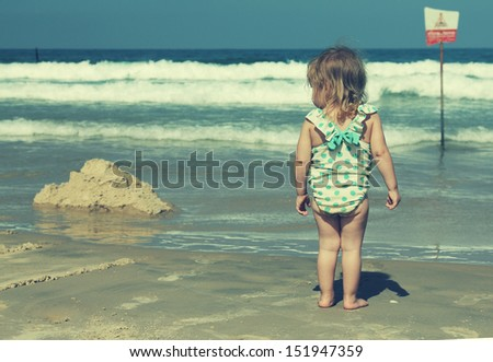 little girl on blue sea shore in summer vacation - stock photo