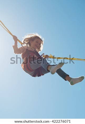 Little girl on bungee trampoline with cords. Place for text. - stock photo