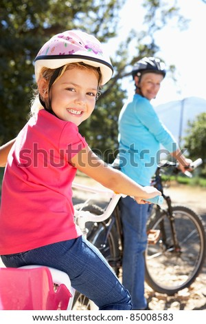 Little girl on country bike ride with grandma - stock photo