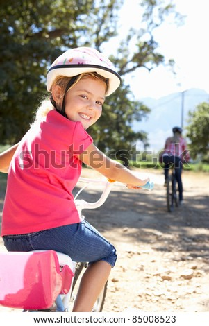 Little girl on country bike ride with mom - stock photo