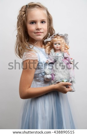 little girl on light Coloured background playing with a doll - stock photo