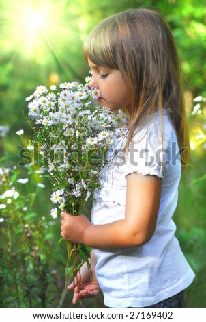 Little girl on meadow with wild flower - stock photo
