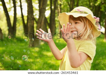 little girl on nature with soap bubbles - stock photo