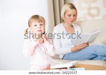 Little girl on phone in living room, mother in background
