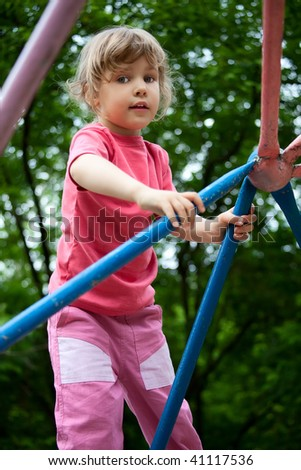 Little girl on pipes on playground