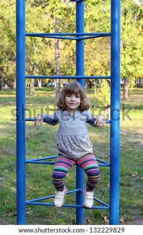 little girl on playground in park - stock photo