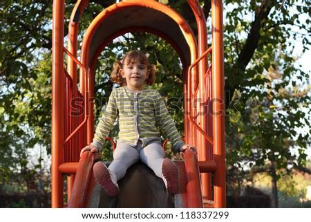 little girl on playground slide - stock photo