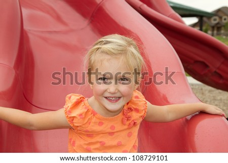 little girl on red slide outdoor shot