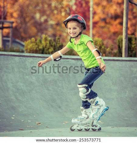 Little girl on roller skates in helmet at a park - stock photo