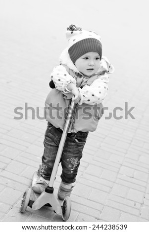 little girl on scooter in the park  ( black and white ) - stock photo