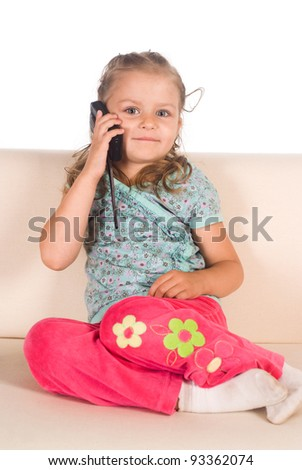 little girl on sofa with a phone - stock photo